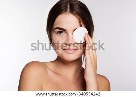 Beautiful women with flawless skin is cleaning her face with cotton pads - stock photo
