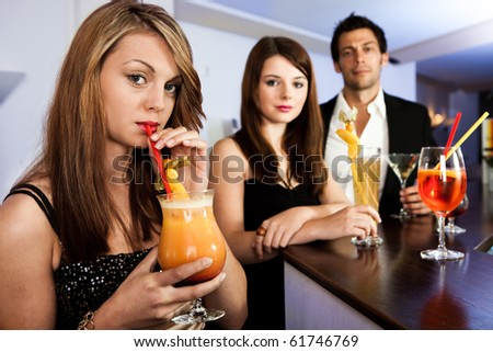 Beautiful women with friends at the bar. Drinking tequila sunrise - stock photo