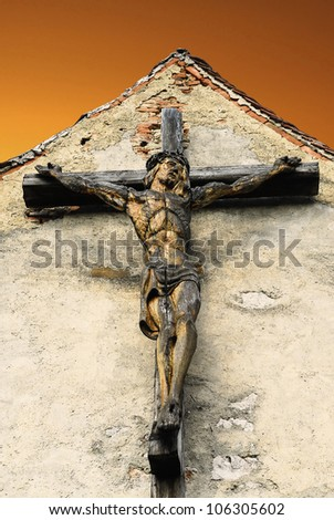 Beautiful wood cross with jesus crucifixion,on a yellow background, ideal for easter or christmas - stock photo