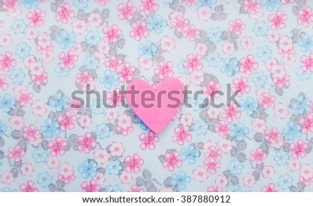 Beautiful wood sewing button scrap-booking heart shaped love pink on a delicate floral background, background flowers for postcard, place for text. Figure heart wood handmade,Selective focus - stock photo