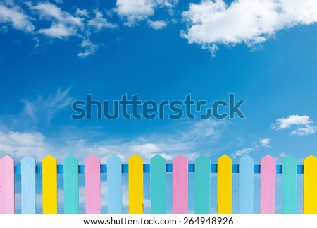 Beautiful wooden fence on a blue  sky background. - stock photo