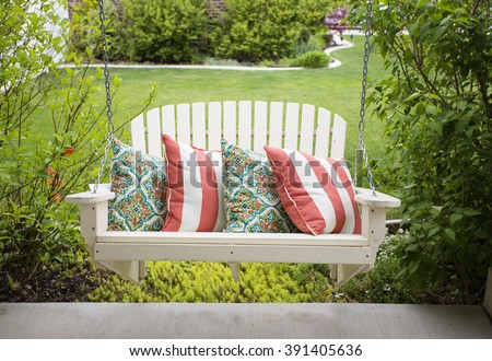 Beautiful wooden front porch swing with comfortable pillows - stock photo