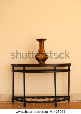 Beautiful wooden handmade vase on table near the wall