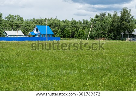 Beautiful wooden house behind blue fence with sunny meadow before. Staroyurievo village, Tambovsky region, Russia.  - stock photo