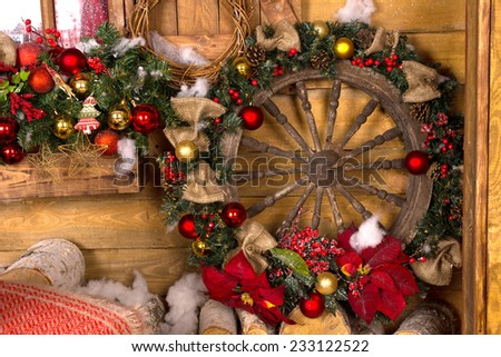 Beautiful Wooden Nautical Ship Wheel Christmas Wreath, with Red Flowers, Brown Ribbons and Red and Gold Balls, Leaning on Wooden Wall. - stock photo
