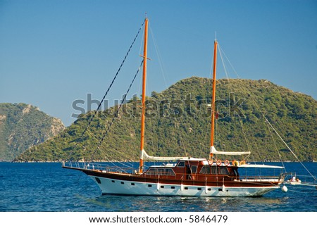 Beautiful Yacht against green mountain - stock photo