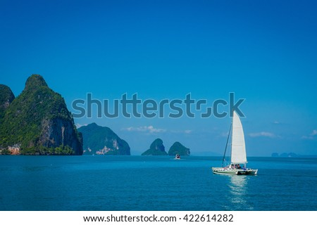 Beautiful yacht in sea with blue sky and mountains on background, peaceful atmosphere - stock photo