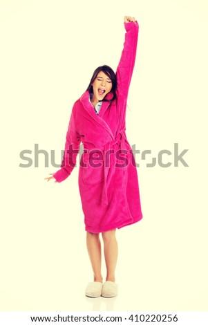 Beautiful yawning woman in pink bathrobe. - stock photo