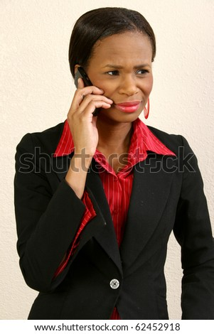 Beautiful 25 year old african american woman in suit on cellphone. - stock photo