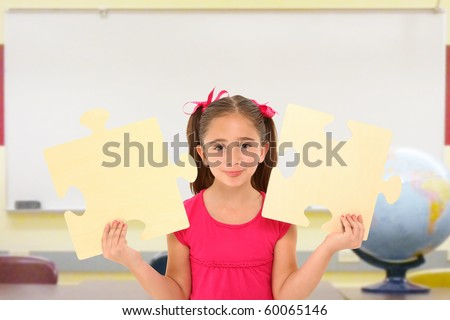 Beautiful 7 year old girl holding two large puzzle pieces in school classroom. - stock photo