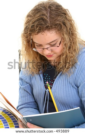 Beautiful 12 Year Old Girl Writing In Notebook.  Curly blonde hair and glasses.  Shot in studio.