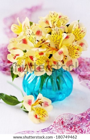 beautiful yellow flowers in a blue glass vase on a table.  - stock photo