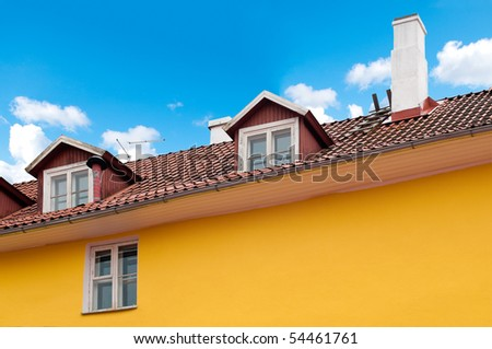 beautiful yellow old house with blue cloudy sky in background (Tallinn, Estonia, Europe) - stock photo