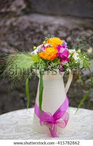 Beautiful yellow rose, pink alstroemeria, wax flower, white spray rose, green foliage flower arrangement in a jug. Wedding decor. Outdoor table decor - stock photo