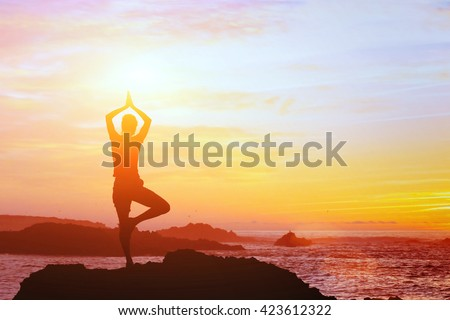 beautiful yoga background, silhouette of woman on the beach at sunset, mindfulness - stock photo
