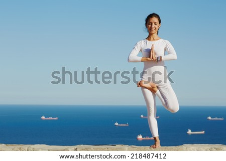 Beautiful yoga with amazing view of sea on background, pretty healthy woman with perfect body stand in one of yoga pose and looking to the camera with smile, feeling neatly with yoga - stock photo