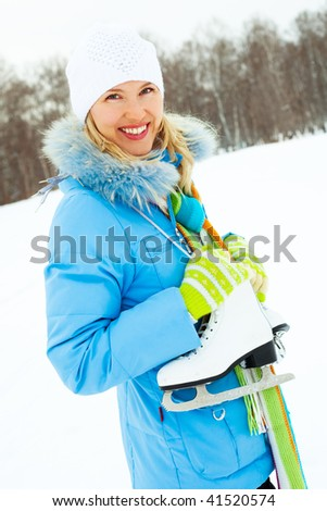 beautiful yougn blond woman wearing warm winter clothes going to ice skating - stock photo