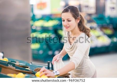 Beautiful youn woman shopping for fruits and vegetables in produce department of a grocery store/supermarket (shallow DOF; color toned image)