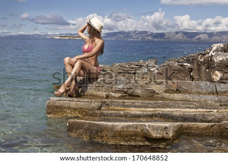 Beautiful, youndg girl at the sea side sitting on the rock - stock photo
