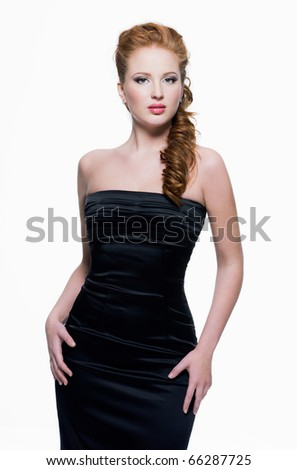 Beautiful young adult sensual woman in black dress posing on white background