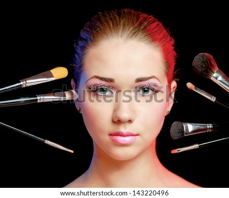 Beautiful young adult woman holds the make-up brushes near attractive face. - stock photo