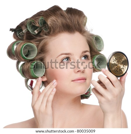 Beautiful young adult woman in hair roller looking in mirror - close-up portrait