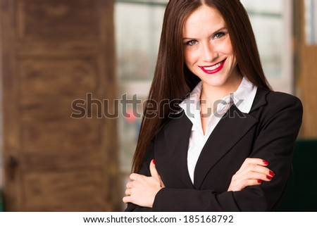 Beautiful young adult woman looks right at camera in the office