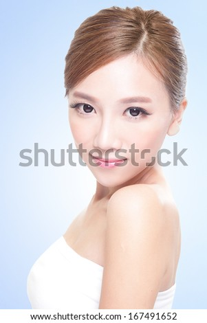 Beautiful young adult woman with clean fresh face, blue background, asian - stock photo