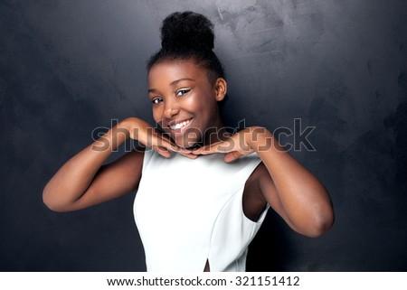 Beautiful young african american girl posing in studio, looking at camera. - stock photo