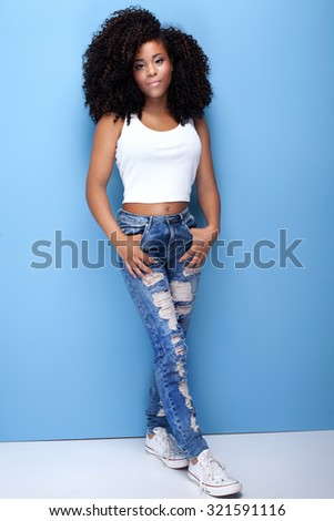 Beautiful young african american girl posing on blue background. Girl with afro looking at camera. - stock photo
