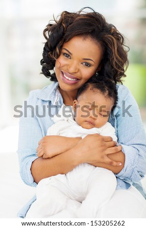 beautiful young african american mother and sleeping baby girl - stock photo