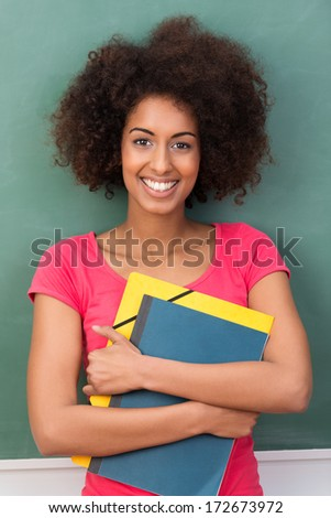 Beautiful young African American student clasping her files containing class notes to her chest as she stands smiling at the camera - stock photo