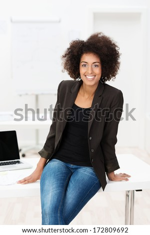 Beautiful young African American student with an afro hairstyle sitting on top of her desk in her jeans grinning happily at the camera - stock photo