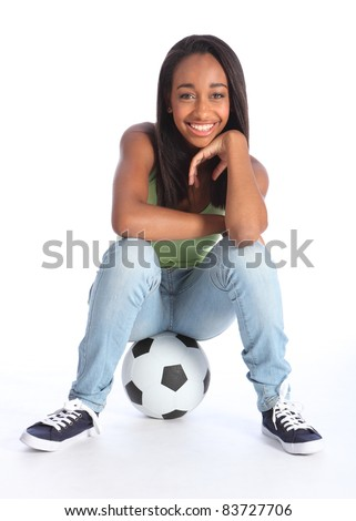 Beautiful young African American teenage school girl soccer player, sitting on a football relaxing. Girl wearing blue jeans and casual vest and has a big happy smile. - stock photo