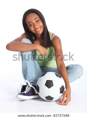 Beautiful young African American teenage school girl soccer player, sitting on the floor with a football. Girl wearing blue jeans and casual vest and has a big happy smile. - stock photo