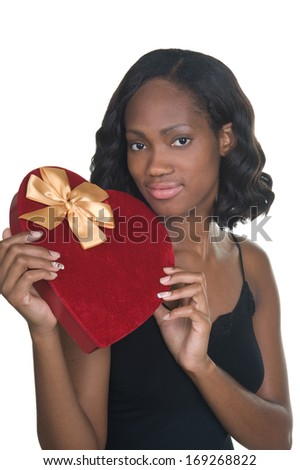 Beautiful young African-American woman holding a heart shaped chocolate box for Valentine's Day - stock photo