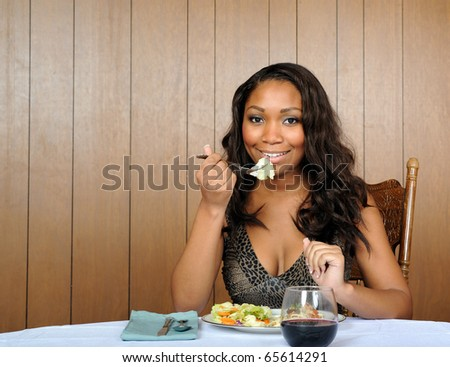 Beautiful young African American woman in animal print dress eating dinner - pasta and salad - vintage feel with wood paneling - stock photo