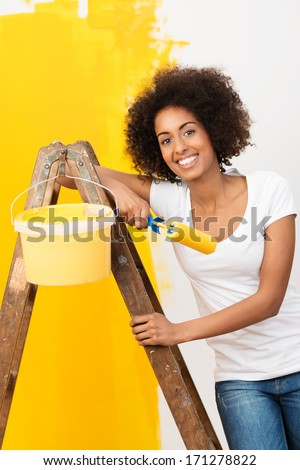 Beautiful young African American woman with a lovely smile doing home renovations standing on a wooden stepladder with a paint roller and bright orange paint as she paints the wall - stock photo