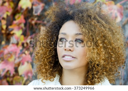 Beautiful young African American woman with afro hairstyle and green eyes wearing white winter dress with autumn leaves in the background. - stock photo