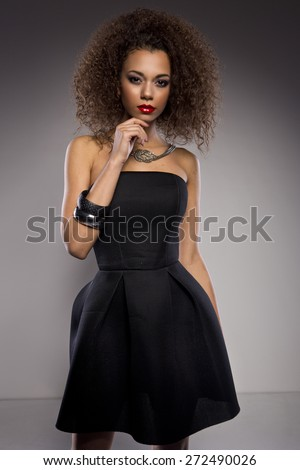 Beautiful young African American woman with afro in a fresh dark short summer dress posing holding up one edge of the flared skirt with a provocative expression, on a dark grey background - stock photo