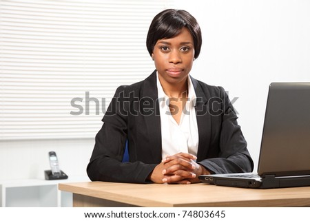 Beautiful young African American woman working in office sitting to her desk with a serious, stern expression. - stock photo
