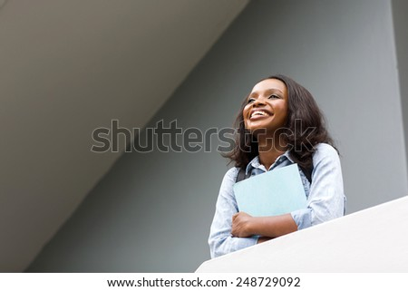 beautiful young african college girl looking up - stock photo