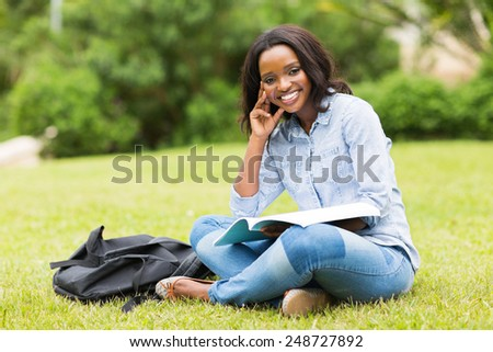 beautiful young african college girl sitting on grass - stock photo