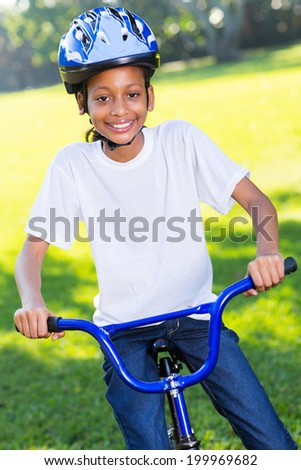 beautiful young african girl riding a bike outdoors - stock photo