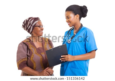 beautiful young african nurse helping senior woman with medical form - stock photo