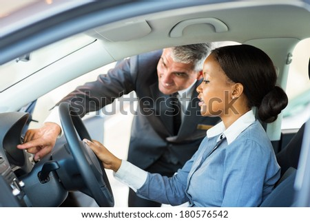 beautiful young african woman buying a car at dealership - stock photo