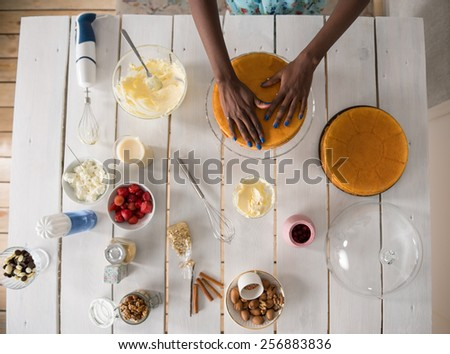 Beautiful young african woman cooking cake at kitchen. Top view - stock photo