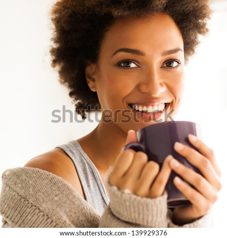 Beautiful young African woman enjoying a cup of coffee. - stock photo