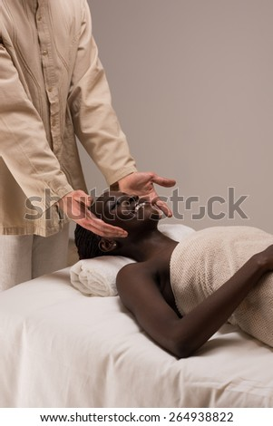 Beautiful young african woman enjoys facial massage in a luxury spa resort - stock photo