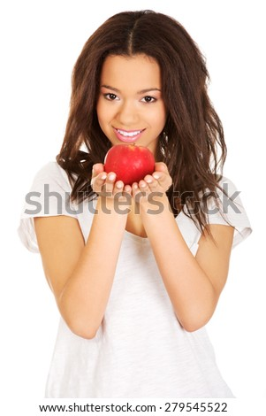 Beautiful young african woman holding an apple. - stock photo